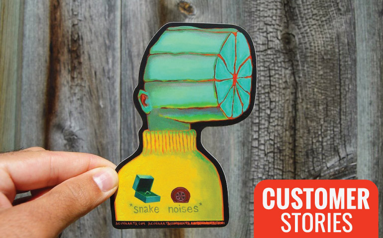 Hand-holding-Snake-Noises-Sticker-in-front-of-wood-fence-for-StickerGiant-Customer-Stories-blog