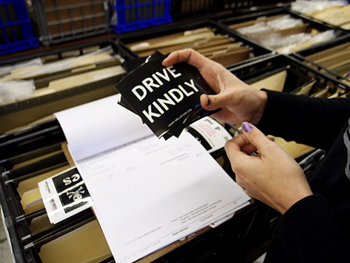 Custom square shaped stickers that say Drive Kindly, originally printed by StickerGiant